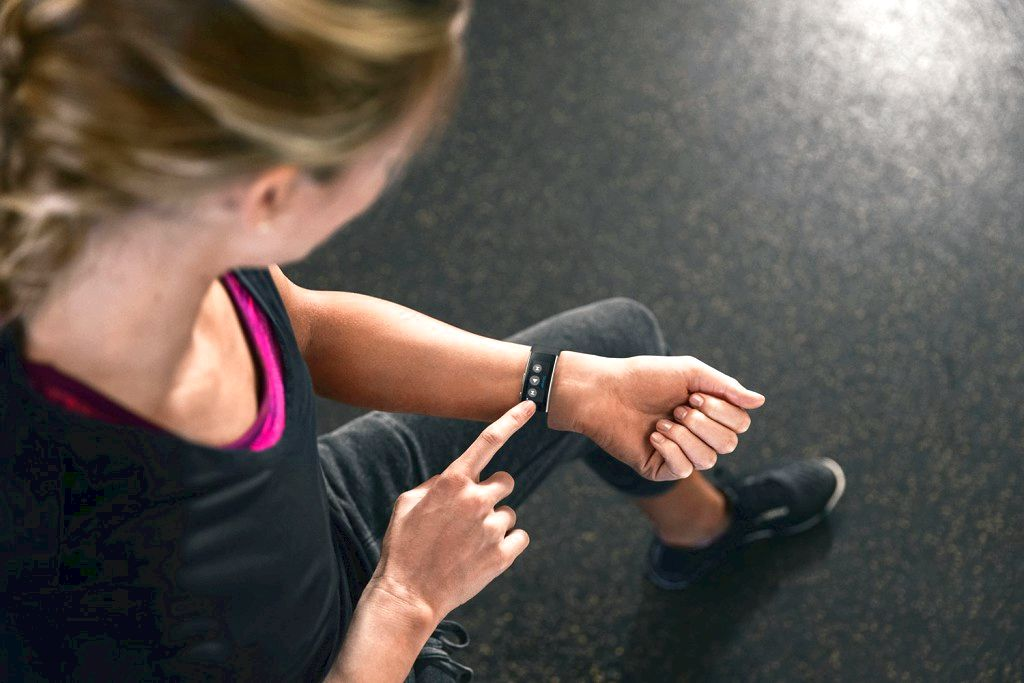 A girl is using the new Microsoft Band and music controls at the gym
